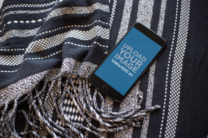 Mockup of a Space Gray iPhone Lying on a Wool Blanket a21513