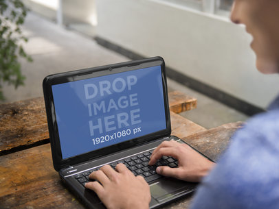Young Man Using his HP Laptop on an Outdoor Table