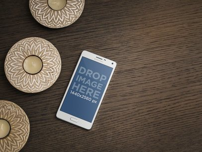 Android Mockup Template Over a Wood Table Next to Some Candles