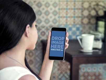 Mockup of a Girl Using Her iPhone 6 Plus Featuring a Colorful Tile Wall