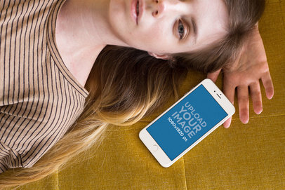 Mockup of an iPhone Lying Next to a Woman on a Mustard Cloth a21501