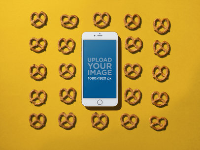 Mockup of an iPhone Lying on a Solid Color Surface with Pretzels a21493