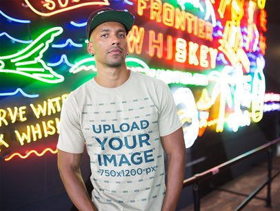 Mockup of a Man Wearing a Round Neck T-Shirt Against Neon Signs a18308