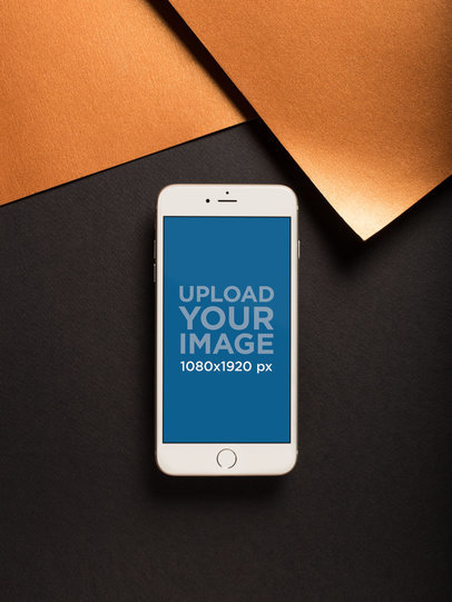 iPhone Mockup on a Black Surface Near Copper Paper Sheets 21492
