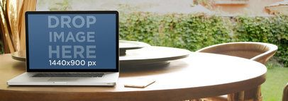 Laptop Mockup Featuring a Macbook Over a Dining Table at the Garden