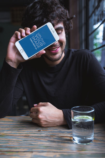 iPhone Mockup of a Man Covering his Face at a Restaurant 21610