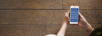 Mockup Template of a Lady Using a White iPhone Over a Wooden Floor