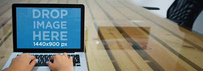 Typing on a Macbook Pro at Conference Room Mockup Template