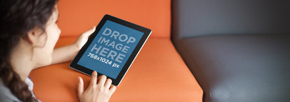 Tablet Mockup of a Young Girl on a Sofa Using a Black iPad