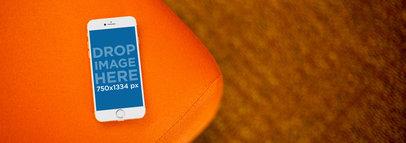 Beautiful Mockup of a White iPhone 6 Over Orange Sofa