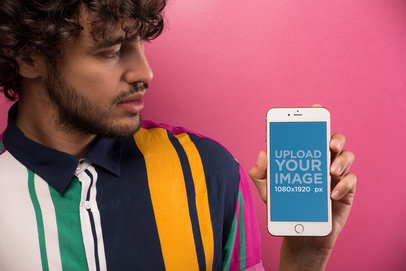 Mockup of a Man Wearing a Vintage Shirt Holding an iPhone Against a Pink Wall 21742