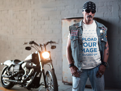 Mockup of a Tattooed Biker Man Wearing a T-Shirt Bandana and Chain In Front of a Motorcycle 20246
