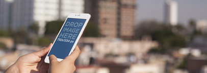 Mockup of a Woman Holding a White iPhone 6 at a Rooftop Terrace
