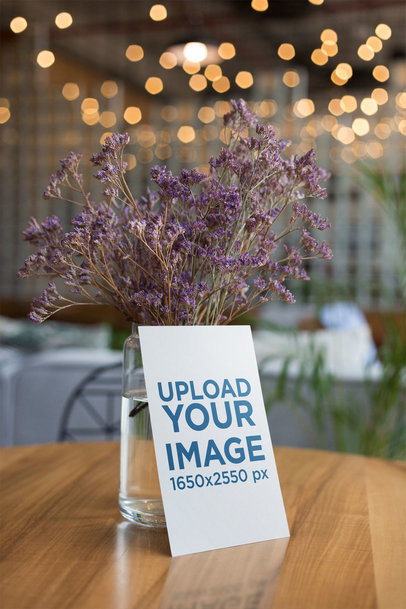 Flyer Mockup Leaning Against a Vase with Purple Flowers 21864