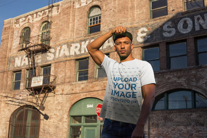 T-Shirt Mockup of a Man Standing in Front of an Old Brick Building 18318