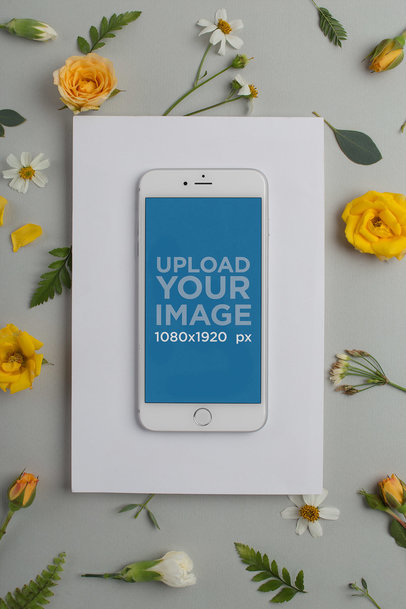 Mockup of a Silver iPhone Over a White Surface with Yellow and White Flowers in the Background 21764