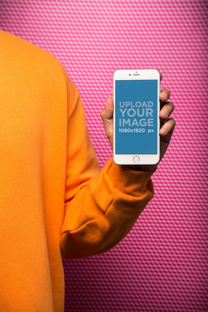 Arm Holding a Silver iPhone Mockup In Front of a Textured Background 21775