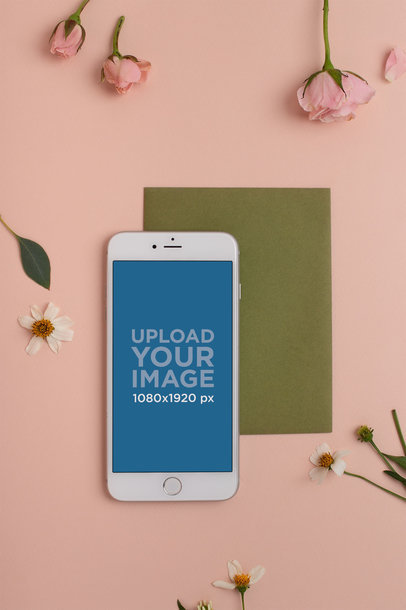 Mockup of a Silver iPhone on a Pink Surface with a Green Cardboard and Small Flowers 21759