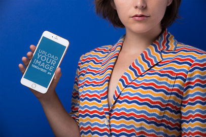Gold iPhone 8 Mockup of a Young Woman in a Colorful Striped Shirt Against a Blue Background 21832