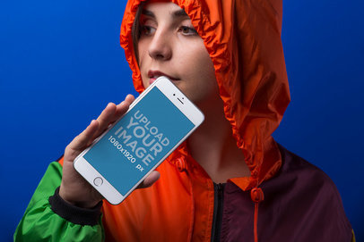 iPhone 8 Plus Mockup Featuring a Young Woman Wearing a Multicolor Hoodie Against a Blue Background 21850