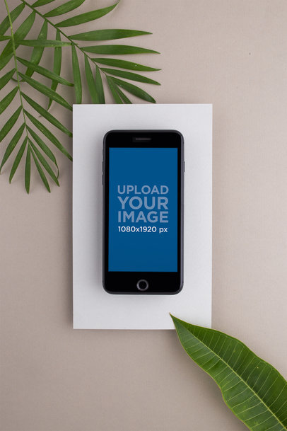 Space Gray iPhone Mockup on a White Rectangular Paper Surrounded by Green Leaves 21824