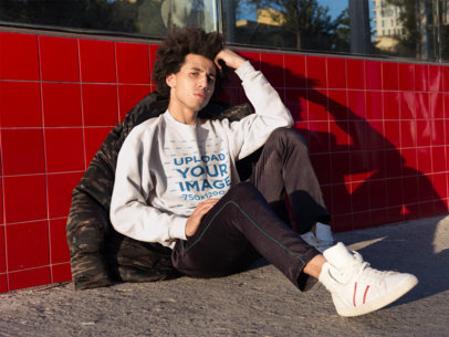 Mockup of a Concerned Man Wearing a Crewneck Sweatshirt Sitting Against a Red Tiles Wall 18334