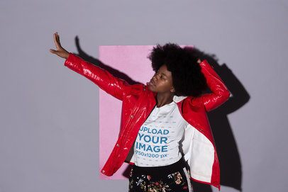 Tee Mockup Featuring a Cool Girl with an Afro Hairstyle Posing Against a Gray Background with a Pink Cardboard 21711
