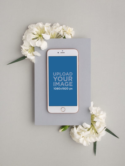 iPhone Mockup on a Gray Cardboard Rectangle Over White Flowers 21984