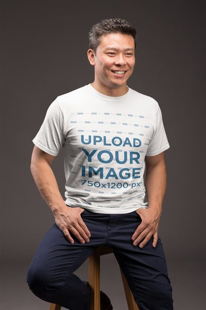 Mockup of a Happy Man Wearing a T-Shirt Sitting on a Stool 21237