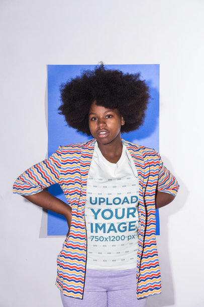 Crew Neck Tee Mockup Featuring a Girl with an Afro Hairstyle and a Multicolored Striped Jacket Against a Sapphire Blue Cardboard 21713