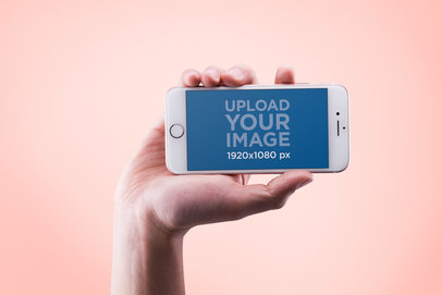 Mockup of a Hand Holding an iPhone in Landscape Position 14133