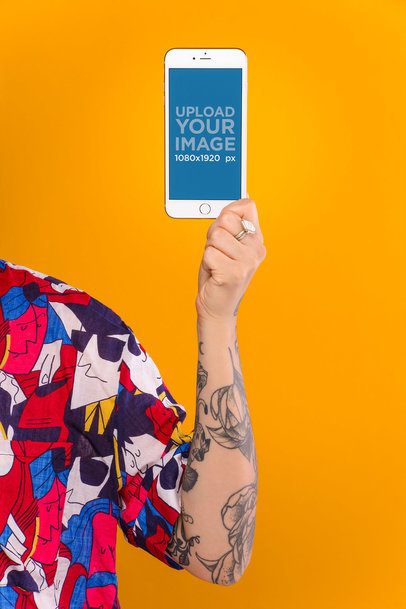 Mockup Featuring a Person with a Tattooed Arm Holding a Gold iPhone 8 Against a Light Orange Background 21963