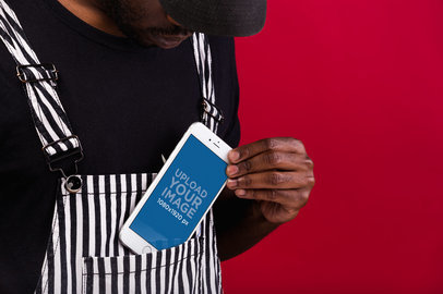 iPhone 8 Plus Mockup Featuring a Man Wearing a Black and White Striped Overall 22084