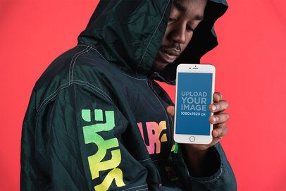 Mockup of a Man in a Fashion Windbreaker Jacket Showing a Silver iPhone 8 Against a Bright Red Wall 22091