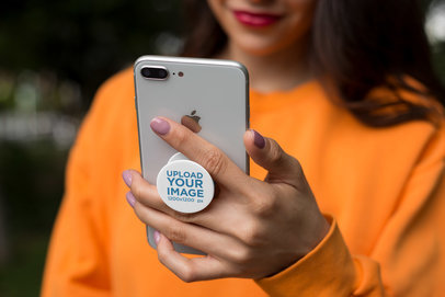 PopSocket Mockup Featuring a Woman in an Orange Sweatshirt 22067