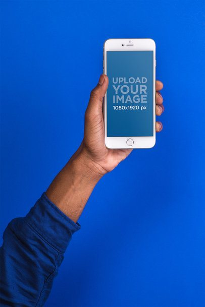 Mockup Featuring the Hand of a Man Holding a Silver iPhone 8 Against a Cobalt Blue Background 22090