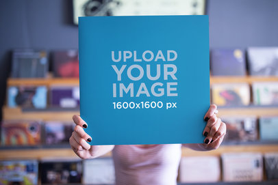 Mockup of a Girl Holding a Vinyl Cover in Front of Her Face with a Blurry Background 22092