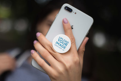 Mockup Featuring a Girl's Hand Holding a Silver iPhone 8 with a PopSocket 22062
