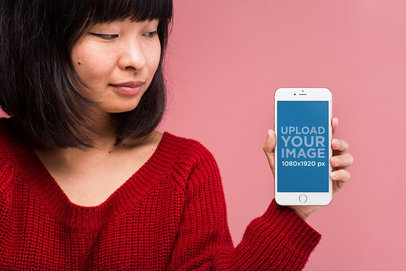 Gold iPhone 8 Mockup Featuring a Woman in a Red Sweater Against a Light Pink Wall 22161