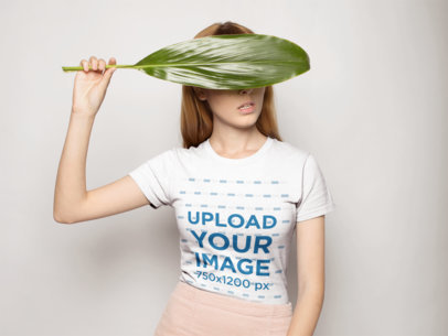 T-Shirt Mockup of a Strawberry Blonde Woman Covering Her Eyes With a Leaf 18387