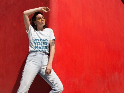 Mockup of a Woman Wearing a T-Shirt in Front of a Bright Red Wall 20044