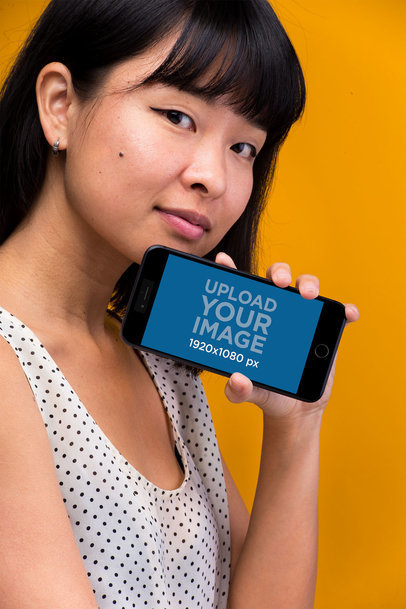 iPhone 8 Plus Mockup Held by a Woman In Front of an Orange Backdrop 22176