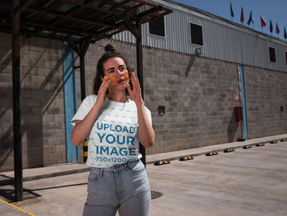 T-Shirt Mockup of a Woman Standing in Front of a Warehouse 20045
