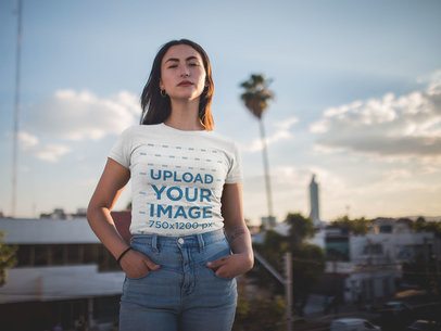 T-Shirt Mockup of a Woman Standing in Front of a City Skyline 19693