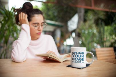 Mockup of a Coffee Mug on a Table in Front of a Woman Reading a Book 22422