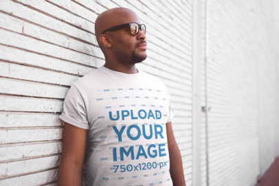 T Shirt Mockup of a Middle-Aged Man with Sunglasses Against a White Textured Wall 20775