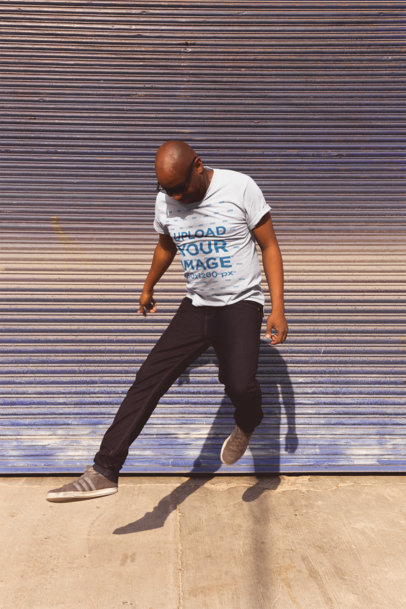 Round-Neck Tee Mockup of a Bald Man Jumping Against a Garage Door 20780
