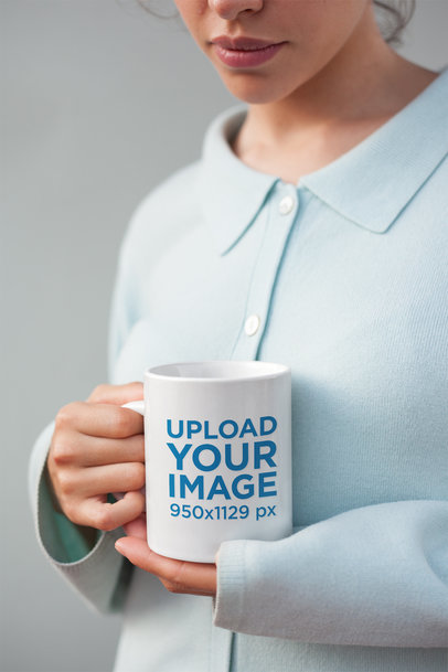 Mockup of a Coffee Mug Held by a Woman Wearing a Blue Sweater 22446