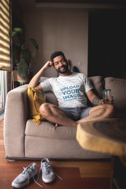 T-Shirt Mockup of a Man Sitting on a Couch Smiling at the Camera 21343