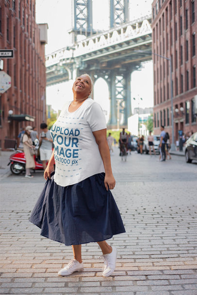 Mockup of a Woman Wearing a Plus-Size T-Shirt In Front of the Brooklyn Bridge 22560